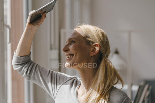 Lächelnde Frau, die ihre Augen mit Tablette abschirmt — Stockfoto