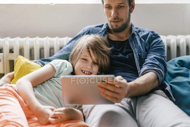 Батько і син дивляться фільм на планшеті вдома — стокове фото