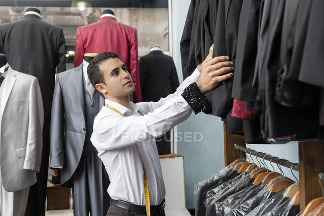 Tailor tidying up suit jackets in tailor shop — Stock Photo