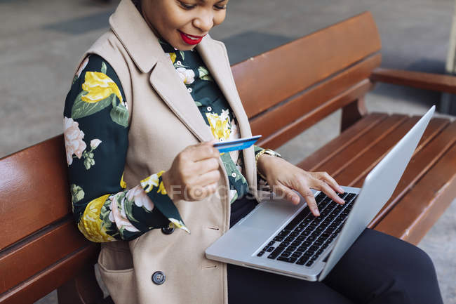 Businesswoman sitting on bench, using laptop and credit card — Stock Photo