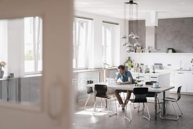 Hombre sentado en la mesa en la cocina y trabajando en el ordenador portátil - foto de stock