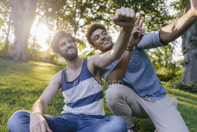 Two happy multicultural friends posing for selfie in park — Stock Photo