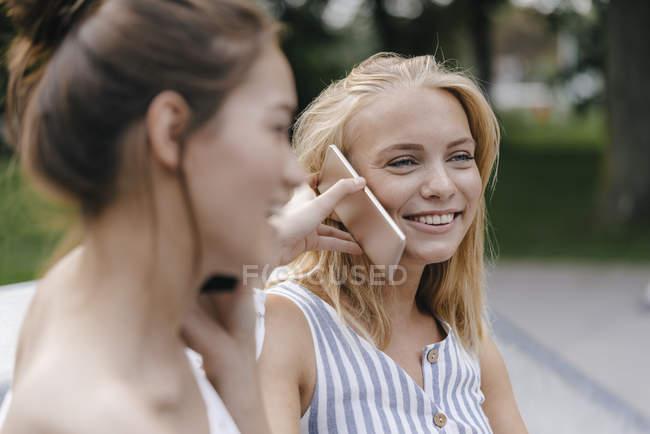 Due giovani donne felici con il cellulare all'aperto — Foto stock