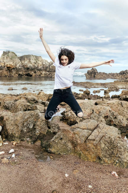 Happy brunette woman jumping on beach with rocks — Stock Photo