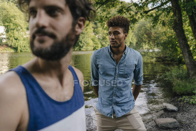 Two multicultural friends looking sideways near lake — Stock Photo