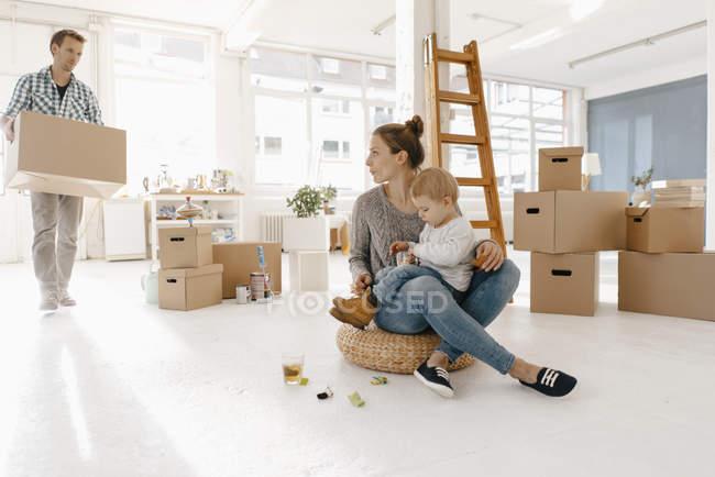 Famille emménageant dans la nouvelle maison avec le père portant la boîte en carton — Photo de stock