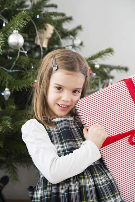 Ritratto di bambina sorridente che regge il regalo di Natale — Foto stock