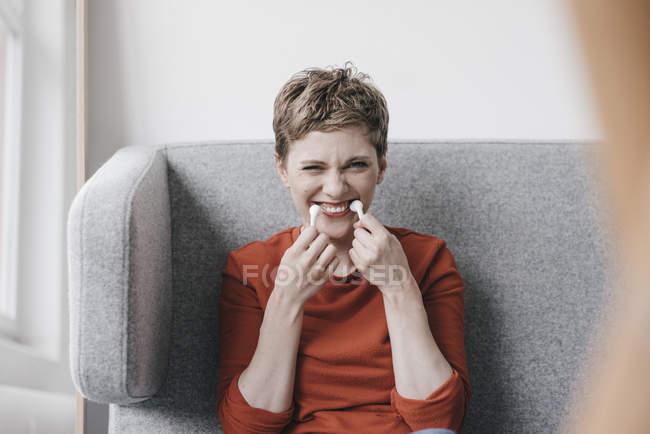 Femme espiègle faisant semblant d'avoir des dents sans fil d'écouteur — Photo de stock