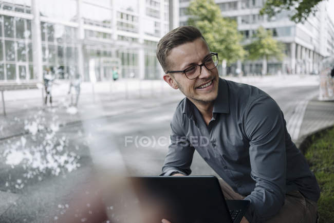 Ritratto di giovane uomo d'affari ridente con computer portatile all'aperto — Foto stock