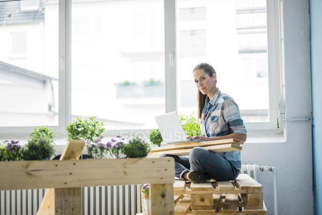 Donna ristrutturando la sua nuova casa con pallet, utilizzando laptop — Foto stock