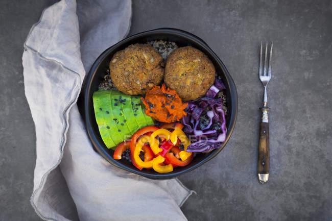 Lunchschüssel mit Quinoa, Rotkohl, Paprika, Avocado, Quinoa-Frittern, Ajvar und schwarzem Sesam — Stockfoto
