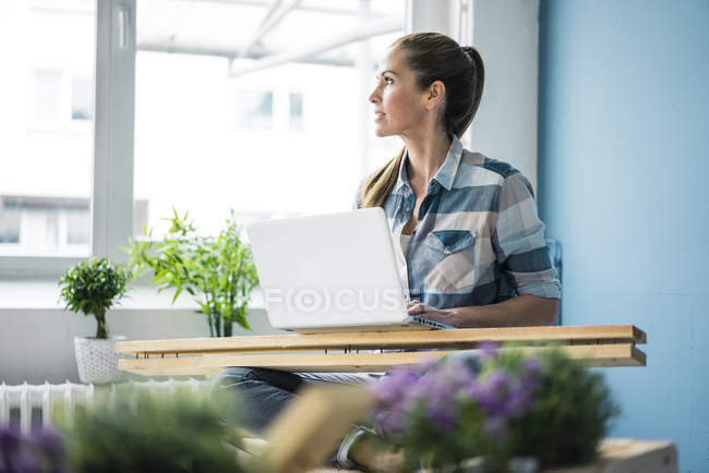 Woman refurbishing her new home with pallets, using laptop — Foto stock