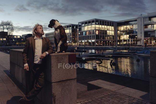 Anziano in piedi con il cane al lago in serata — Foto stock