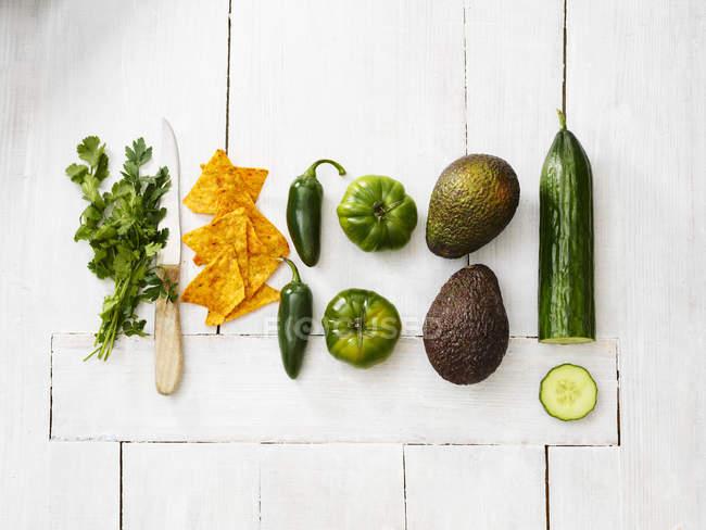 Avocados, grüne Tomaten, Jalapeño-Paprika, Gurken, Petersilie, Küchenmesser und Tortilla-Chips auf weißem Holz — Stockfoto