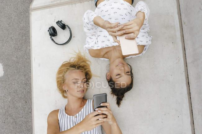 Duas jovens mulheres com telefones celulares e fones de ouvido descansando em um parque de skate — Fotografia de Stock