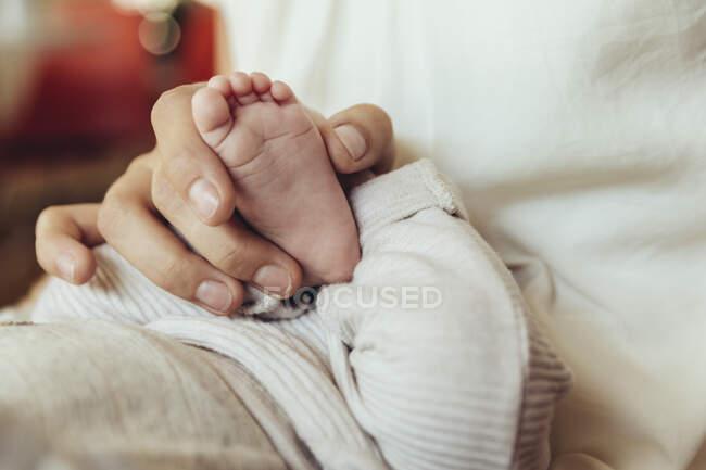 Close-up de mãe segurando bebê recém-nascido? s pé — Fotografia de Stock