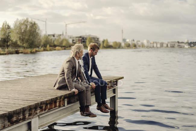 Due uomini d'affari seduti sul molo al lago — Foto stock