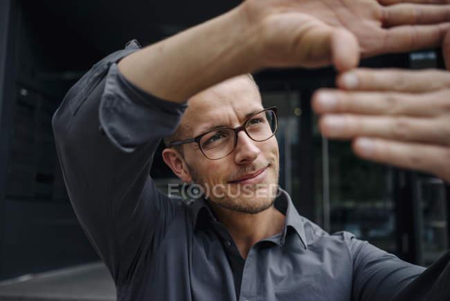 Porträt eines lächelnden Geschäftsmannes, der Fingerrahmen macht — Stockfoto
