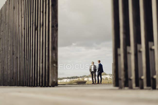 Due uomini d'affari in piedi sul molo al lago e parlare — Foto stock