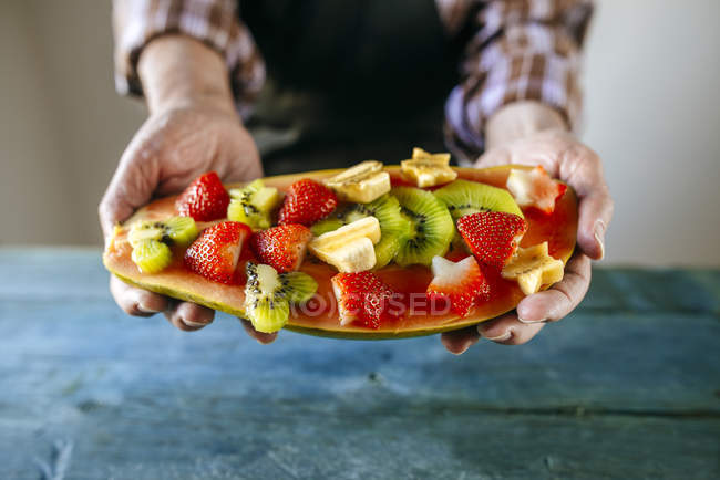 Close-up of man's hands with half papaya with pieces of banana, kiwi and strawberries — Stock Photo