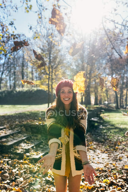 Portrait of a beautiful happy woman having fun with leaves in an autumnal forest — Stock Photo