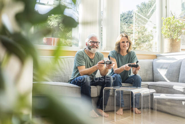 Happy mature couple sitting on couch at home and playing video game — Stock Photo