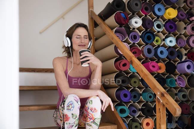 Entspannte reife Frau hören Musik neben einer Auswahl an Yogamatten — Stockfoto