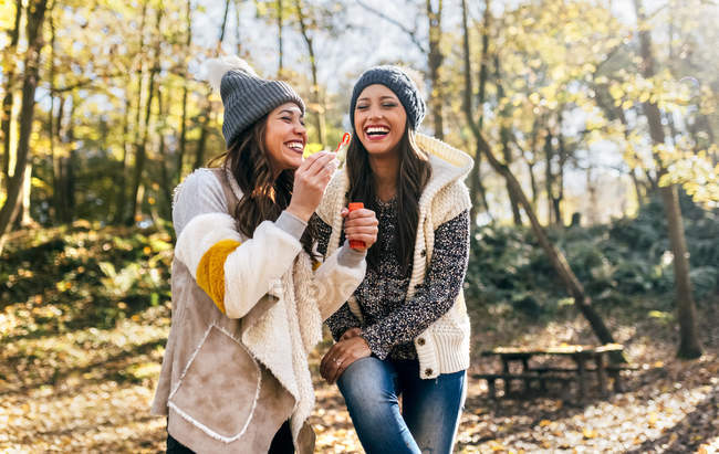 Two beautiful women having fun with soap bubbles in an autumnal forest — Stock Photo