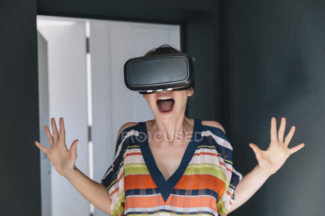 Amazed woman wearing VR glasses and making a crazy face — Stock Photo