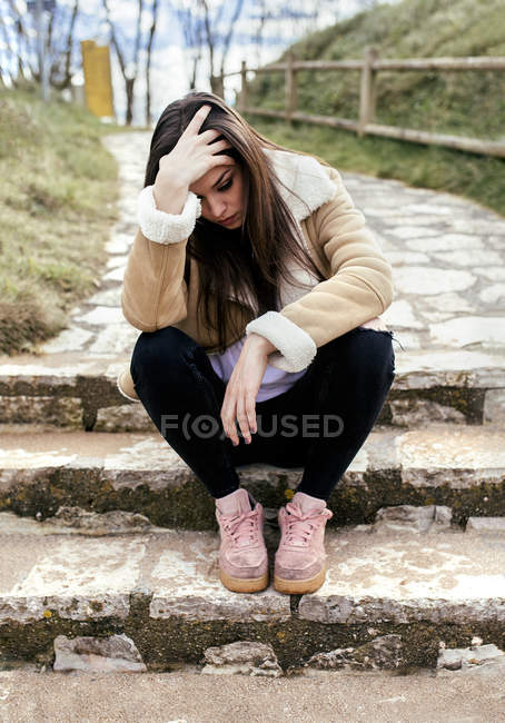 Sad young woman sitting outdoors on steps and keeping hand on head — Stock Photo
