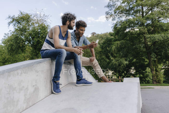 Two multicultural friends sharing cell phone in skatepark — Stock Photo