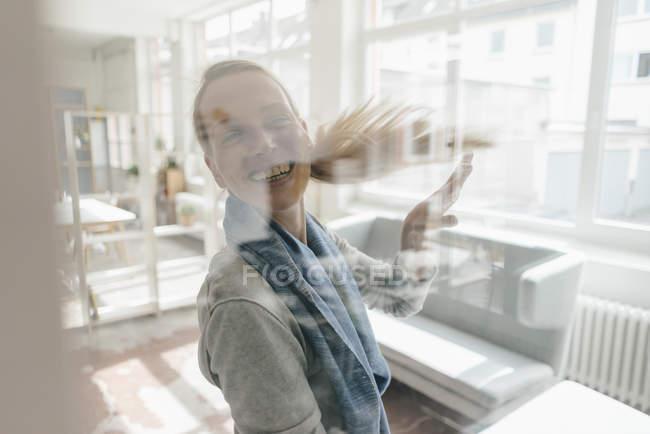 Porträt einer fröhlichen Frau hinter Glasscheibe auf einem Dachboden — Stockfoto