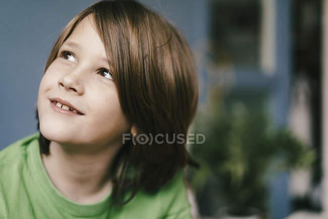 Портрет улыбающегося мальчика, смотрящего вверх — стоковое фото