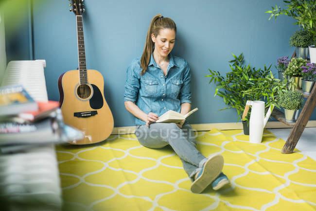 Donna rilassante nella sua casa con piante in vaso, leggendo un libro — Foto stock