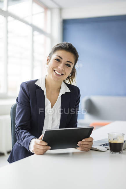 Portrait of happy businesswoman with tablet sitting at desk in office — Stock Photo