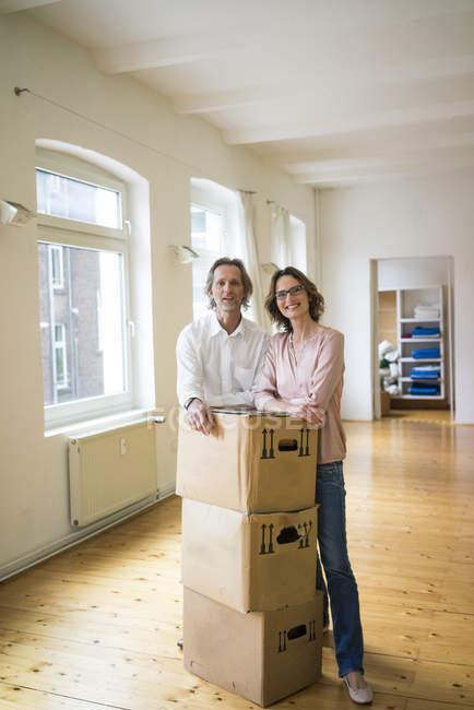 Couples mûrs de sourire restant dans la pièce vide avec des boîtes en carton — Photo de stock