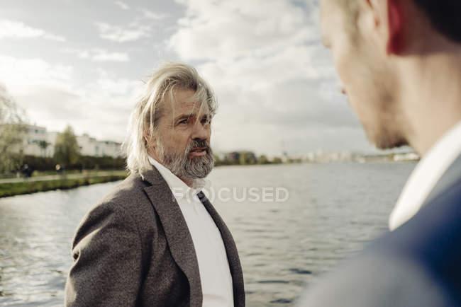 Anziano uomo d'affari parlare con l'uomo in primo piano al lago — Foto stock