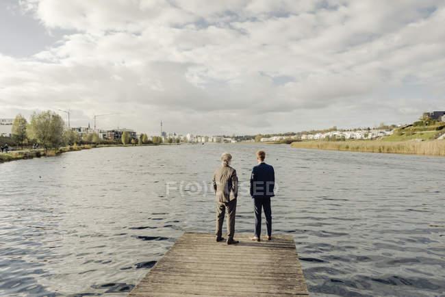 Due uomini d'affari in piedi sul molo al lago — Foto stock