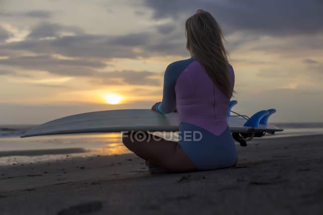 Индонезия, Бали, молодая женщина с доской для серфинга сидит на пляже на закате — стоковое фото