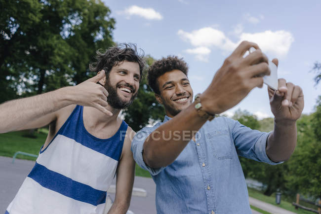 Two happy multicultural friends taking selfie in skatepark — Stock Photo