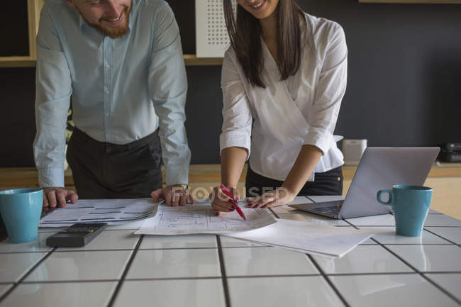 Smiling man and woman studying plans on table at home — Stock Photo