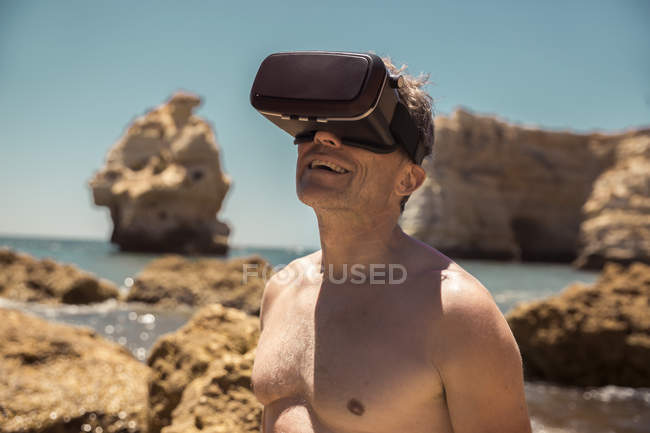 Mature man wearing VR glasses between rocks on beach — Stock Photo