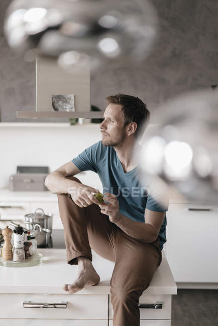 Pensive man sitting on kitchen counter and looking at distance — Fotografia de Stock