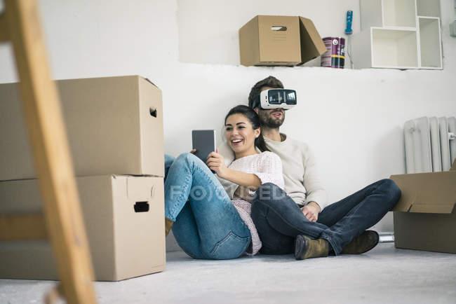 Pareja sentada en un nuevo hogar con un hombre usando gafas VR - foto de stock