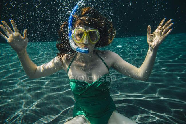 Retrato de mujer con gafas de buceo y snorkel bajo el agua en una piscina - foto de stock