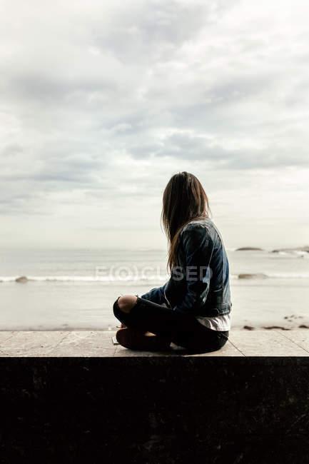 Vista para trás, mulher sentada em uma parede olhando para o mar — Fotografia de Stock