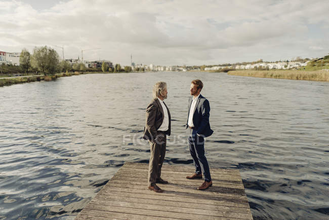 Dos hombres de negocios de pie en el embarcadero en el lago y hablando - foto de stock