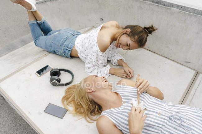 Due giovani donne felici sdraiate sulla rampa nello skate park e che fanno musica — Foto stock