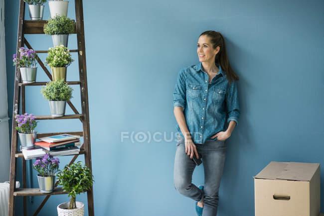 Bella donna nella sua nuova casa, decorata con piante, appoggiata al muro — Foto stock