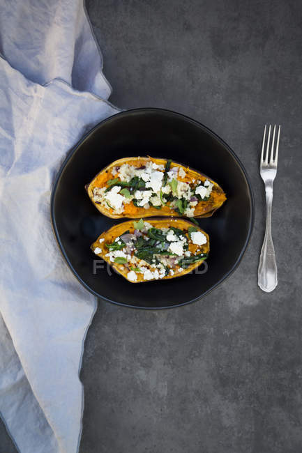 Filled sweet potato with spinach, red onion, couscous, feta and coriander — Stock Photo